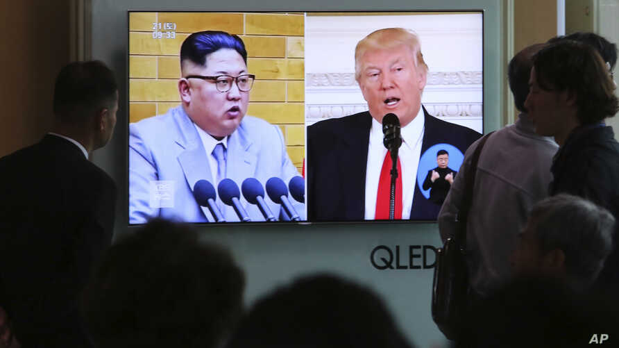 People watch a TV screen showing President Donald Trump, right, and North Korean leader Kim Jong Un during a news program at the Seoul Railway Station, April 21, 2018. North Korea said it has suspended nuclear and long-range missile tests and plans t