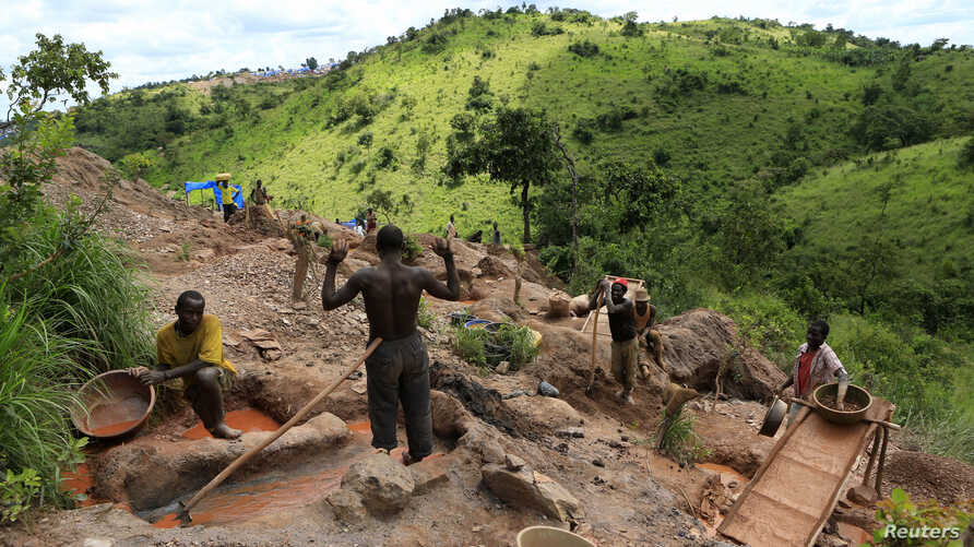 FILE - Gold miners work at an open-pit gold mine in Lukingi village in Mubende district, about 150 km (90 miles) southwest of Uganda's capital Kampala.