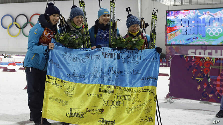 Ukraine's relay team, from left: Vita Semerenko, Juliya Dzhyma, Olena Pidhrushna and Valj Semerenko, with Ukrainian flag with writings on it after winning the gold in the women's biathlon 4x6k relay at the 2014 Winter Olympics, Feb. 21, 2014, in Kras