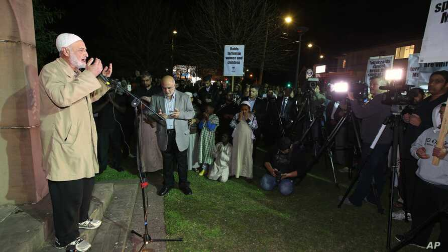 FILE - Members of a Muslim community say a prayer as they gather for a peaceful demonstration at Lakemba in suburban Sydney following raids involving 800 federal and state police officers that came in response to intelligence that an Islamic State gr