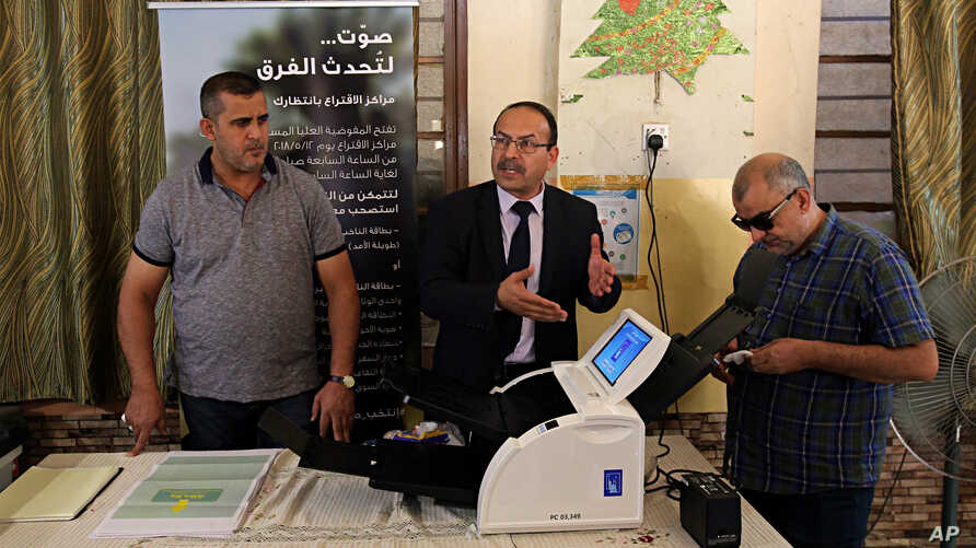 Employees of the Independent High Electoral Commission explain the election process, during a press conference in Baghdad, Iraq, April 30, 2018.