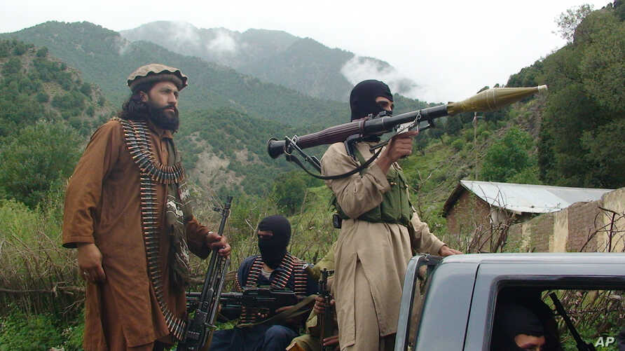 FILE - Militants of the Pakistani Taliban patrol in their then-stronghold of Shawal in the Pakistani tribal region of South Waziristan, Aug. 5, 2012.