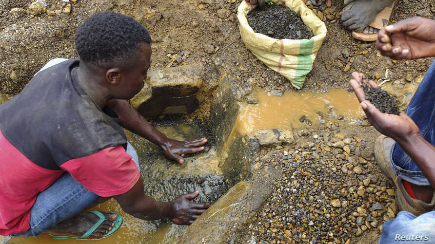 FILE - An artisanal miner washes tin ore before it is bagged up and weighed, ready to be transported to the nearest major town for export in the Kalimbi tin mine near the small town of Nyabibwe, D.R.C.