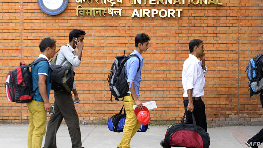 Nepalese migrant workers arrive at the entrance to Tribhuvan International Airport in Kathmandu on September 27, 2013. If the the GCC approves a Kuwaiti proposal, Asian workers coming to Gulf countries to work will undergo mandatory medical screening