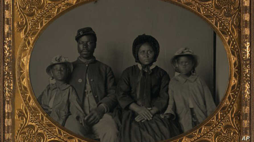 Unidentified African American soldier in Union uniform with wife and two daughters between 1863 and 1865.