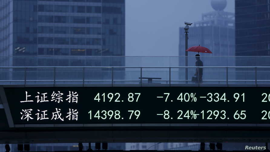 A man walks past an electronic board showing the benchmark Shanghai and Shenzhen stock indices, on a pedestrian overpass at the Pudong financial district in Shanghai, China, June 26, 2015.