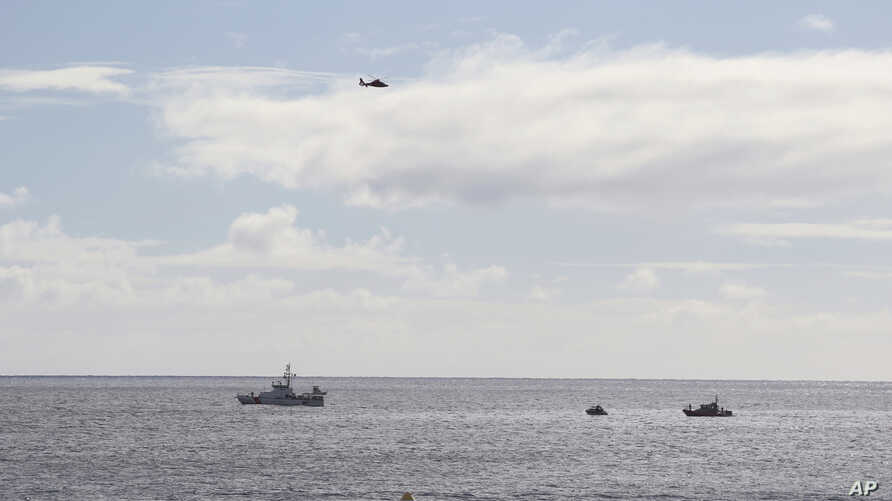 A U.S. Coast Guard helicopter flies over rescue boats at the scene of plane crash off Honolulu, Wednesday, Dec. 12, 2018.