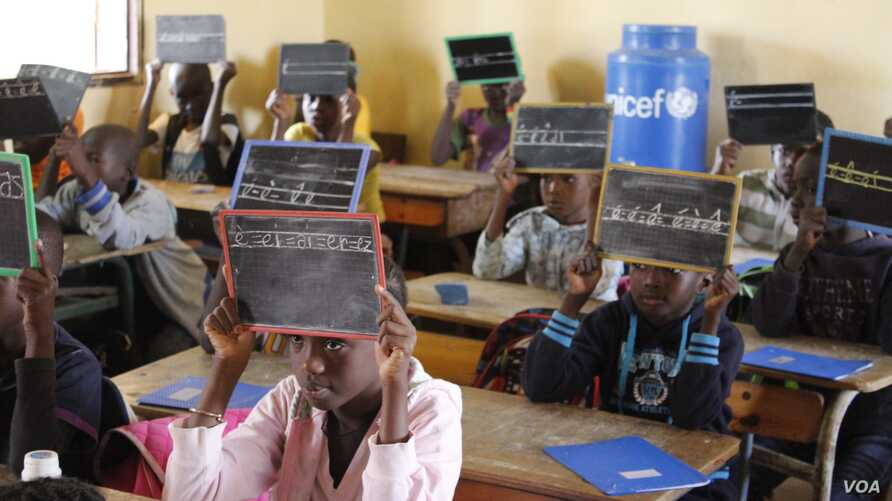 Second-graders in Alieu Samb primary school hold up chalk boards with French conjugations. Dakar, Senegal, Dec. 7 2017. (Photo: Sofia Christensen for VOA)