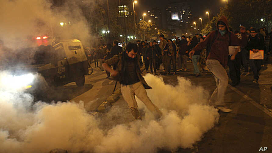 An environment supporter kicks a tear gas canister in Santiago, May 13, 2011, during a rally against hydro-power dam project which will be built at the southern Chilean Patagonia
