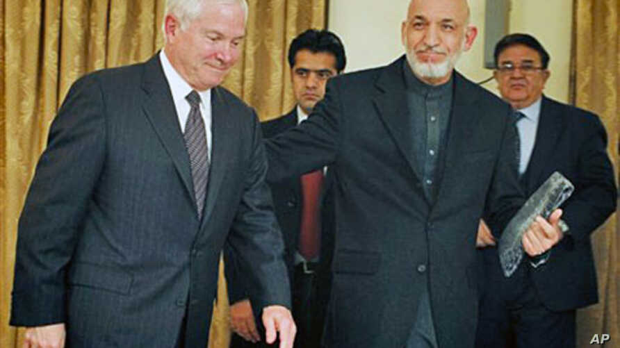 Defense Secretary Robert Gates (L) is escorted by Afghan President Hamid Karzai after a joint press conference at the presidential palace in Kabul, 08 Dec 2010