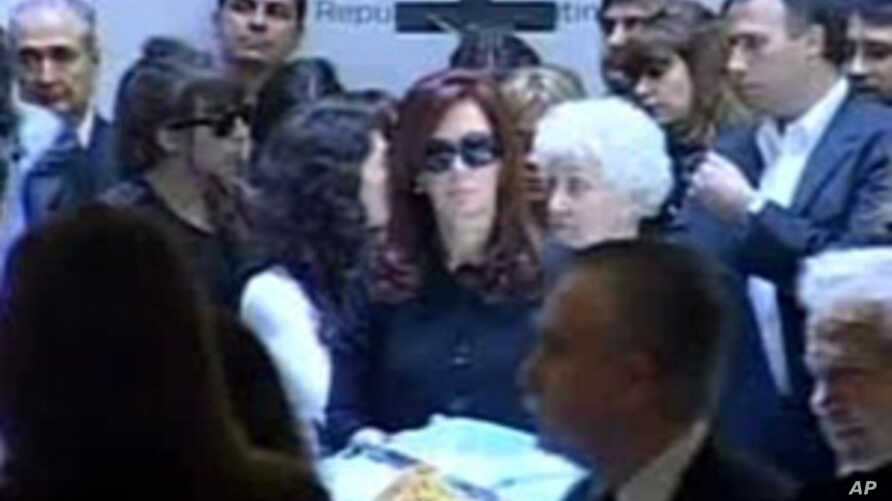 President Cristina Fernandez, center, stands next to the coffin of her husband, former President Nestor Kirchner, as mourners file past in Buenos Aires, Argentina, 28 Oct. 2010