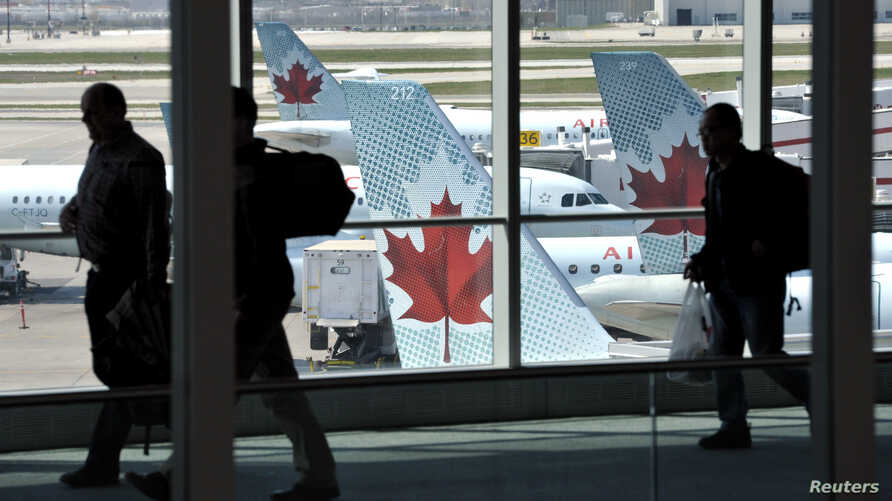 FILE - Passengers walk past Air Canada planes on the runway at Pearson International Airport in Toronto.