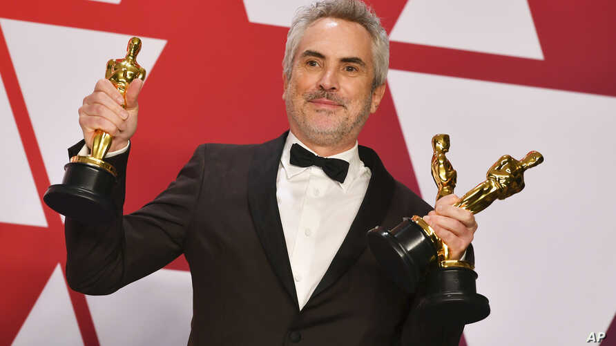 """FILE - Alfonso Cuaron poses with the awards for best director for """"Roma,"""" best foreign language film for """"Roma,"""" and best cinematography for """"Roma"""" in the press room at the Oscars at the Dolby Theatre in Los Angeles, Feb. 24, 2019."""