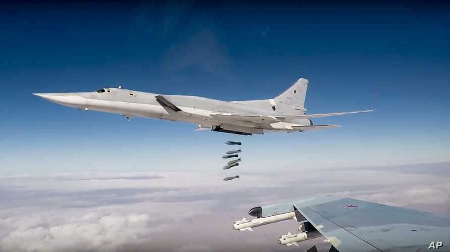 In this photo made from the footage taken from the Russian Defense Ministry official website on Nov. 26, 2017, Russian Tu-22M3 long-range bombers strike Islamic State targets in Syria.