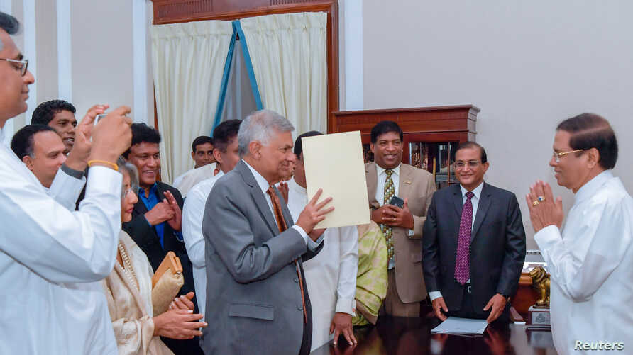 Ranil Wickremesinghe, ousted as prime minister in October, takes his oath for the same post before Sri Lanka's President Maithripala Sirisena during his swearing-in ceremony in Colombo, Sri Lanka, Dec. 16, 2018.
