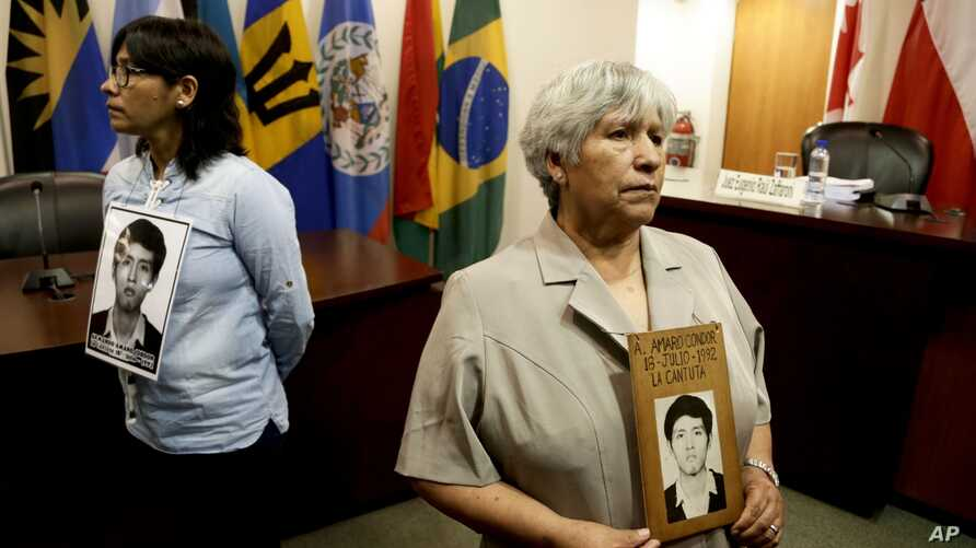 Raida Condor, right, and Carmen Amaro, relatives of Amador Condor, killed during the government of Peru's former President Alberto Fujimori, hold a portrait of him, inside the chambers of the Inter-American Court of Human Rights where judges are anal