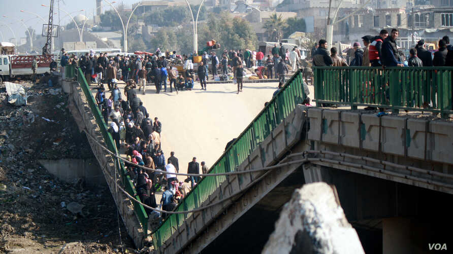 This bridge, like most in Mosul, was blown up by IS militants as Iraqi forces closed in a month ago, and now serves as a makeshift marketplace, Jan. 19, 2017. (H. Murdock/VOA)
