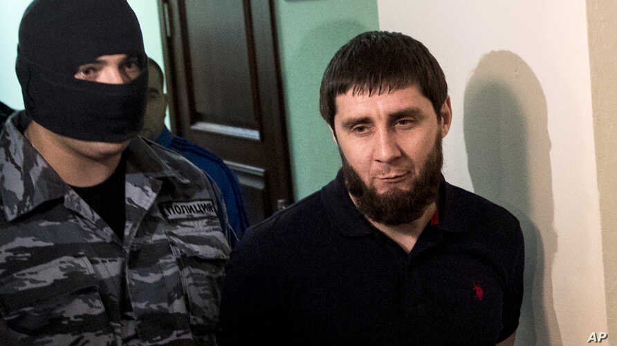 A police officer, left, escorts Zaur Dadaev, one of five suspects held in the killing of Russian opposition politician Boris Nemtsov, is escorted in a court in Moscow, Russia, Monday, Oct. 3, 2016.