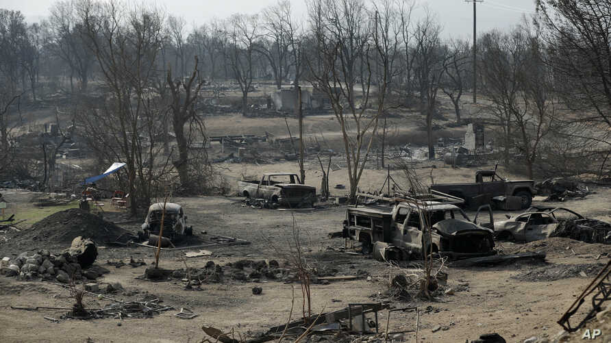 Burned out cars sit in a neighborhood burned in the Carr Fire, Saturday, Aug. 11, 2018, in Redding, Calif.