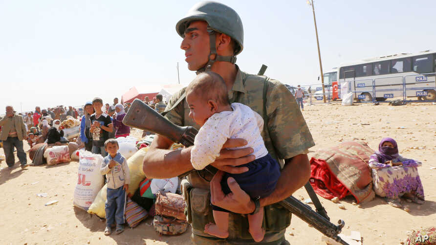 A Turkish soldier holds a lost baby as he looks for its mother, as thousands of new Syrian refugees from Kobani arrive at the Turkey-Syria border crossing of Yumurtalik near Suruc, Turkey, Thursday, Oct. 2, 2014. (AP Photo/Burhan Ozbilici)