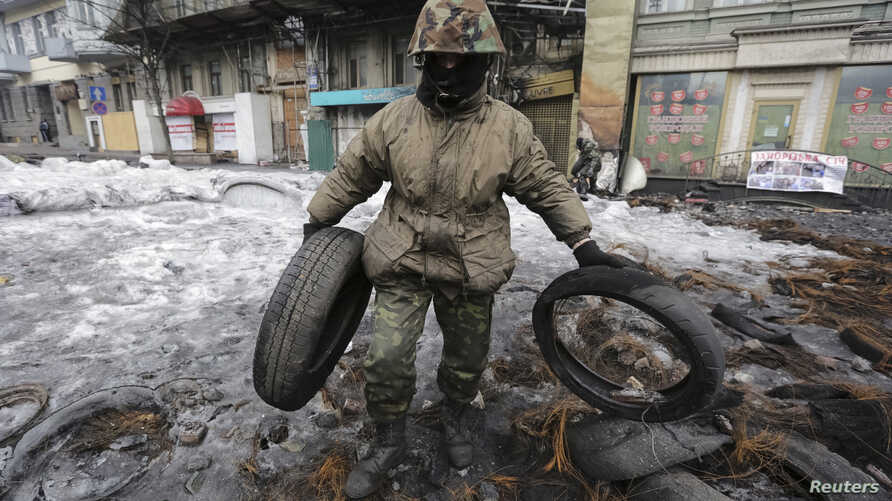 An anti-government protester removes barricades at the site of recent clashes with riot police in Kiev February 16, 2014. Ukrainian anti-government protesters ended a two-month-old occupation of city hall in the capital Kiev on Sunday to meet an amne...