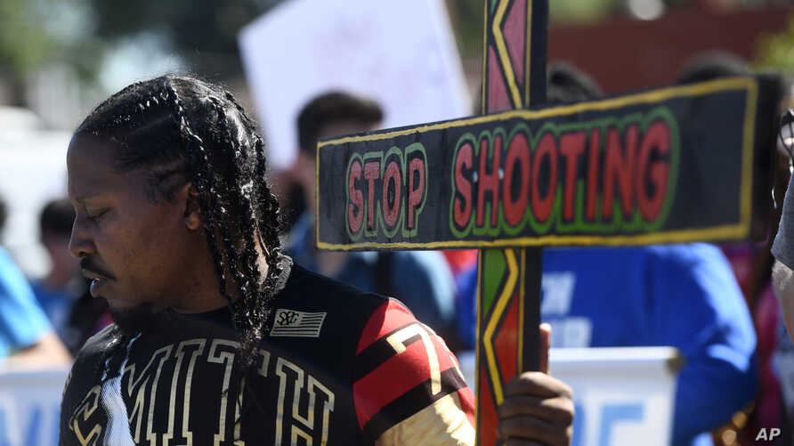 Joseph Saunders carries a cross at a protest July 7, 2018, in Chicago. The protesters were attempting to increase pressure on public officials to address the gun violence that's claimed hundreds of lives in some of the city's poorest neighborhoods.