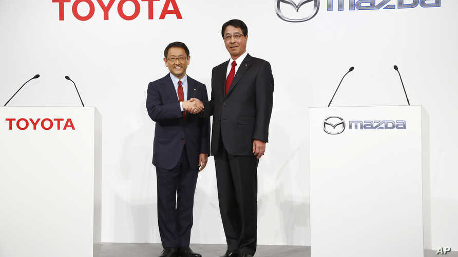 FILE - Toyota Motor Corp. President Akio Toyoda, left, and Mazda Motor Corp. President Masamichi Kogai pose for photographers before a press conference in Tokyo, May, 13, 2015. The Japanese automakers are partnering in electric vehicles with a deal e
