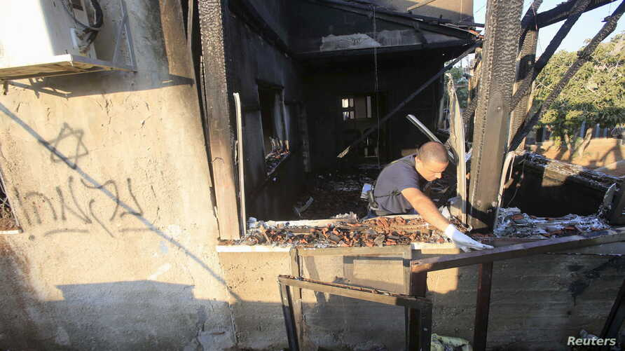 An Israeli police officer inspects a house that was badly damaged from a suspected attack by Jewish extremists on two houses at Kafr Duma village near the West Bank city of Nablus July 31, 2015.