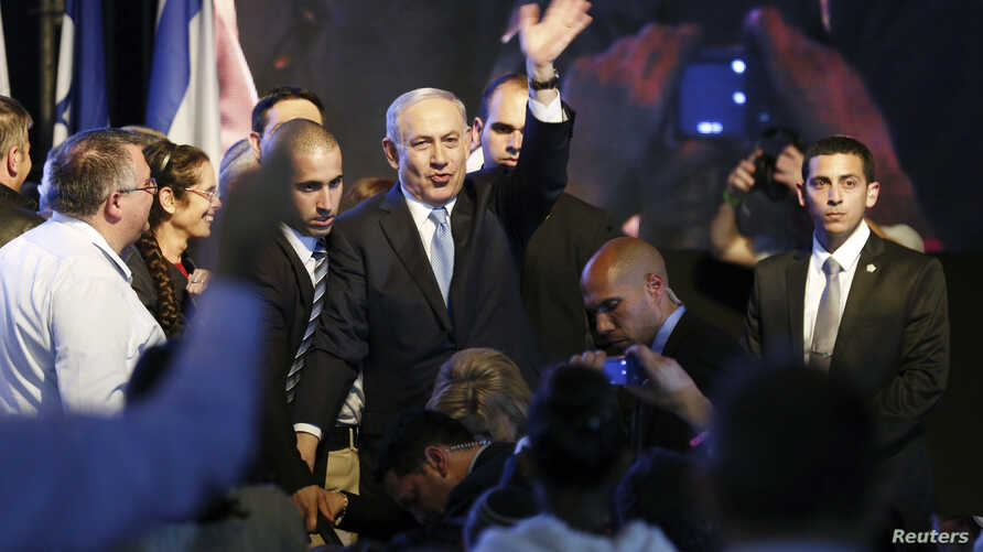 Israeli Prime Minister Benjamin Netanyahu, center, waves to supporters at party headquarters in Tel Aviv, March 18, 2015.