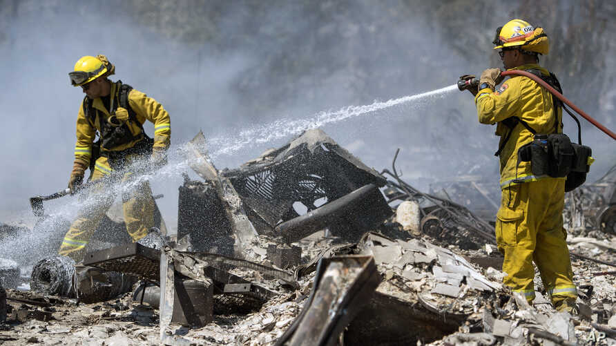 Carlos Orta, right, of Santa Cruz Calfire douses the smoldering remains of a home in Lower Lake, California, Aug. 15, 2016.