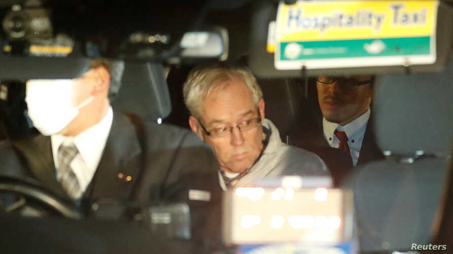 Greg Kelly, the former deputy of ousted Nissan chairman Carlos Ghosn, is seen in the car, as he leaves after being released from a detention center in Tokyo, Dec. 25, 2018.