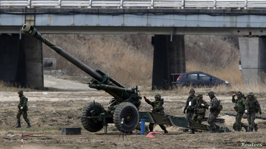 "South Korean soldiers of an artillery unit take part in an artillery drill with 155mm Towed Howitzers as part of the annual joint military exercise ""Foal Eagle"" by the U.S. and South Korea, near the demilitarized zone (DMZ) which separates the two Ko"