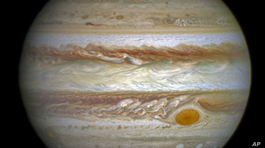 This composite image provided by NASA on Thursday, June 30, 2016 shows auroras on the planet Jupiter. This image produced by NASA using a photograph captured by the Hubble Space Telescope in spring 2014, and ultraviolet observations of the auroras in