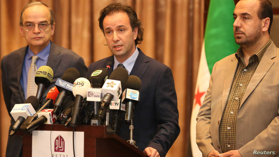 File - Khaled Khoja (center), the head of the Syrian National Coalition, speaks during a press conference as the former Secretary General Nasr Hariri, right, and the former president Hadi Bahra, left, stand next to him, in Istanbul, Turkey, January 2