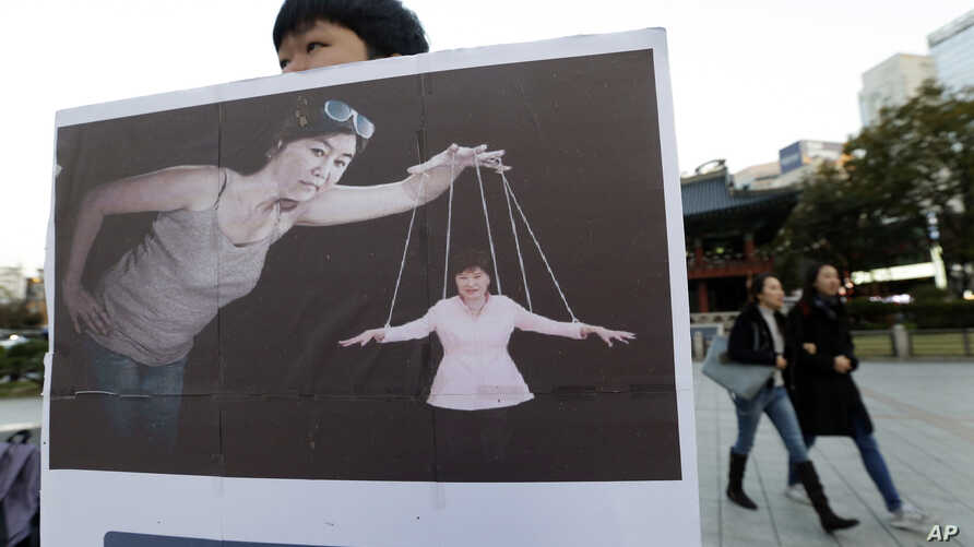 A South Korean college student holds a placard depicting South Korea's President Park Geun-hye, right bottom, as a marionette and Choi Soon-sil, who is at the center of a political scandal, as a puppeteer, in Seoul, South Korea, Nov. 3, 2016. The let...