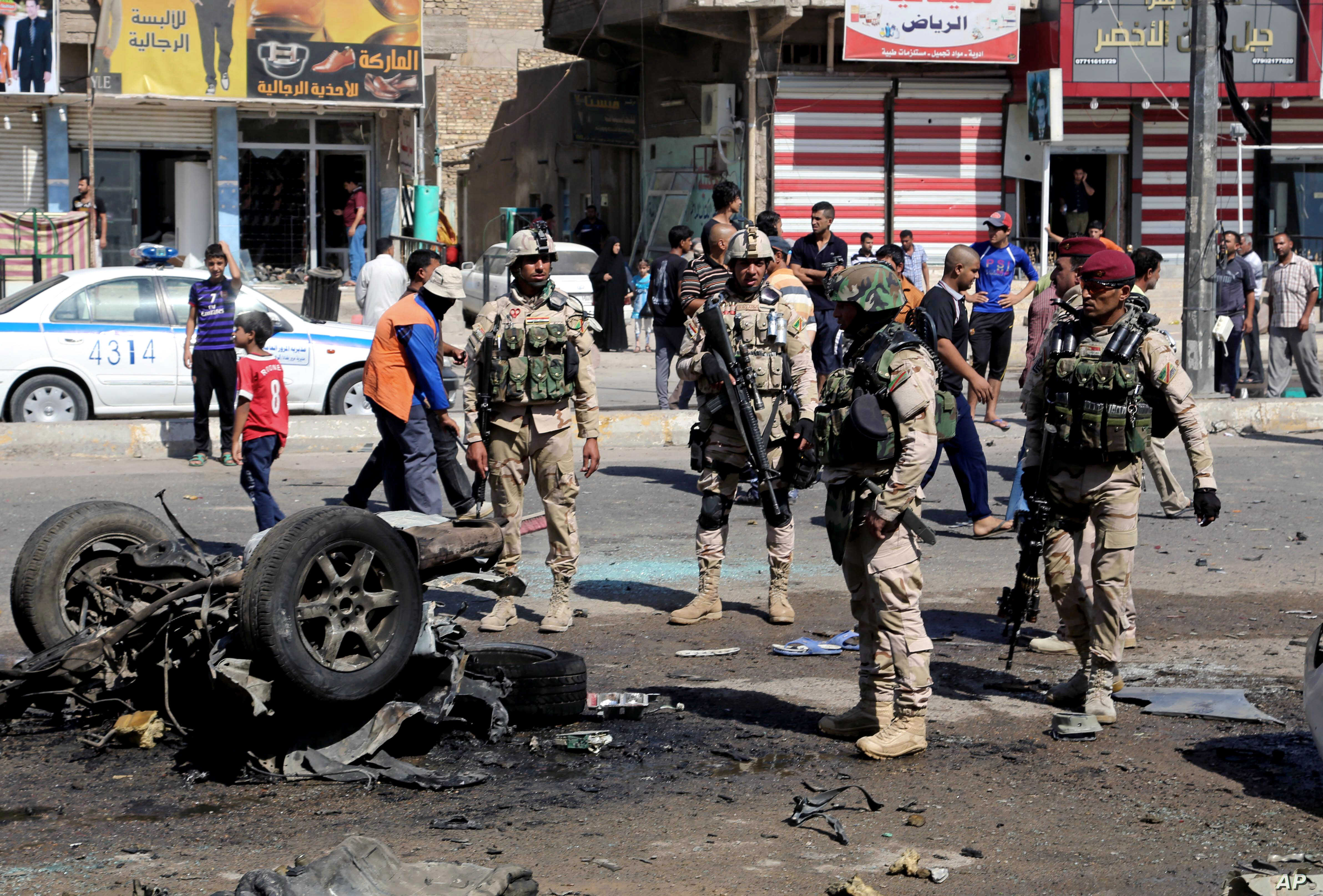 People and security forces inspect the site of a car bomb attack in Sadr City, Baghdad, August 28, 2013.