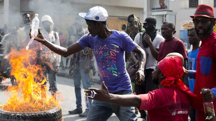 FILE - Demonstrators set barricade on fire during a violent protest in Port-au-Prince, Haiti, Nov. 23, 2018. Thousands of demonstrators clashed with police in Haiti's capital, demanding the ouster of President Jovenel Moise.