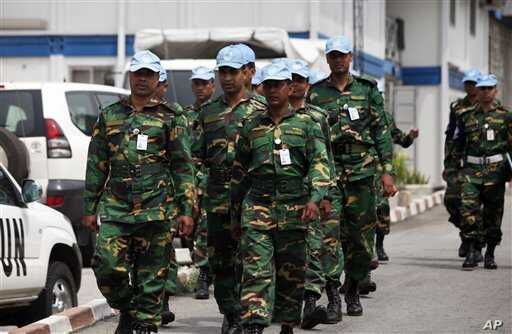 UN troops walk inside the UN Headquarters in Abidjan, Ivory Cost, Friday, Dec. 31, 2010. The United Nations is warning supporters of incumbent leader Laurent Gbagbo that an attack on the hotel where the internationally recognized winner of last month