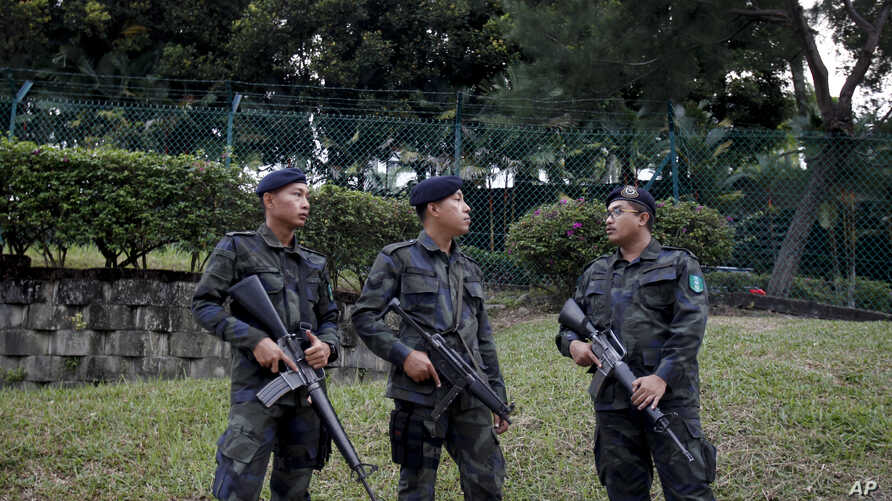 FILE - Police officers stand guard outside a Shah Alam court house at Shah Alam outside Kuala Lumpur, Malaysia on Friday, July 28, 2017.