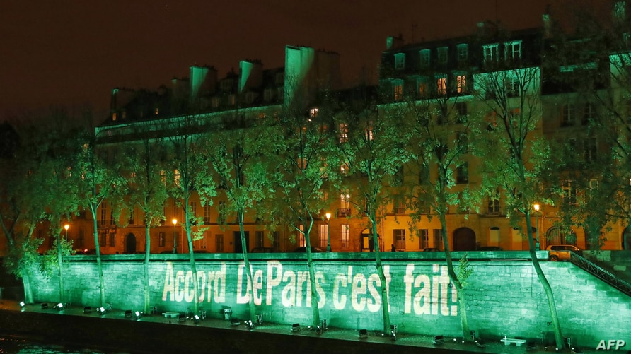 The Ile Saint-Louis is illuminated with the lettering reading 'The Paris accord is done' in Paris, Nov. 4, 2016, to celebrate the first day of the application of the Paris COP21 climate accord.