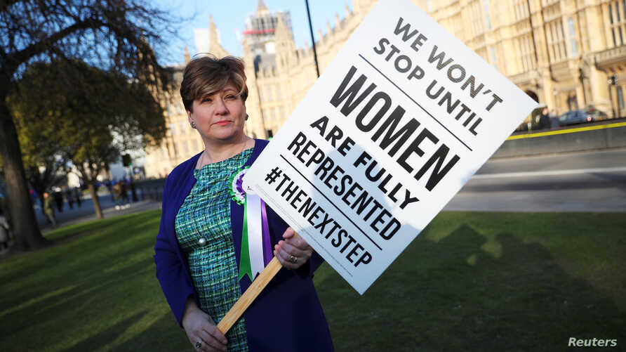 FILE - Labour Party member of Parliament Emily Thornberry holds a placard at an event to mark the 100th anniversary of the enfranchisment of some, but not all women, outside the Houses of Parliament in London, Britain, Feb. 6, 2018.