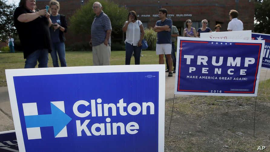 FILE -  early voters stand by campaign signs as they wait in line at a voting location in Dallas.