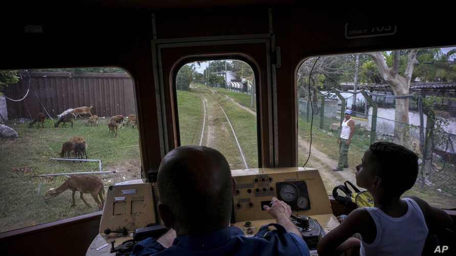 A boy rides next to the engineer of an electric Hershey train in the Casablanca municipality of Havana, Cuba, Aug. 26, 2015.