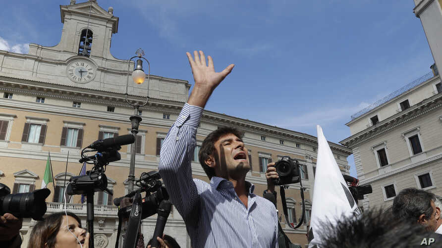 """Five-Star Movement Lawmaker Alessandro Di Battista uses a megaphone to talk with demonstrators of the Liberation of Italy Movement as they stage a protest outside the Italian Parliament against the government-proposed electoral law """"Rosatellum"""" in Ro"""