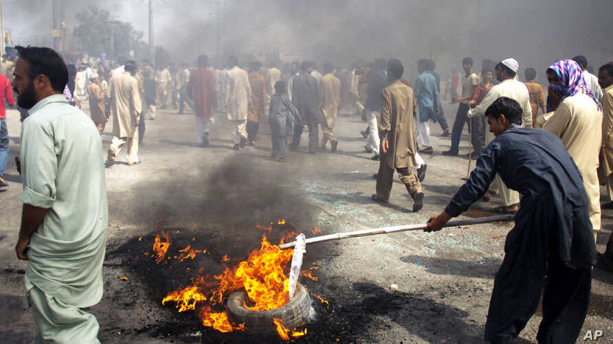 Pakistani protesters burn tires to block the main highway in Rawalpindi, Pakistan, September 21, 2012.