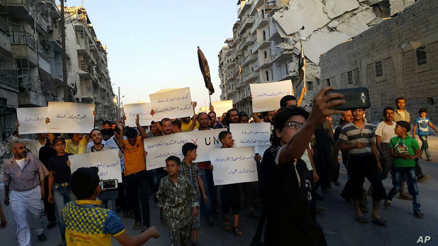 Activists in Syria's besieged Aleppo protest against the United Nations for what they say is its failure to lift the siege of their rebel-held area, Sept. 13, 2016. Dozens of protesters marched in the al-Shaar neighborhood heading toward the Castel...