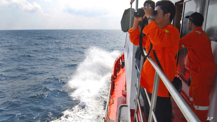A member of Indonesian National Search and Rescue Agency (BASARNAS) uses a binocular to scan the horizon during a search operation for the missing Malaysia Airlines Boeing 777 conducted on the waters of the Strait of Malacca off Sumatra island, Indon