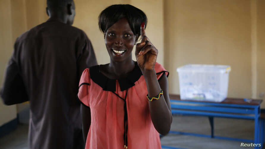 A woman shows her ink-stained finger after casting her ballot at a polling station located in a school during a referendum in the town of Abyei, Oct. 27, 2013.