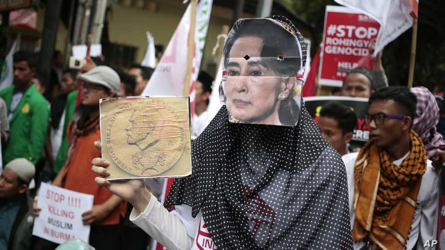 A Muslim woman wears a mask of Myanmar's Foreign Minister Aung San Suu Kyi during a rally against the persecution of Rohingya Muslims, outside the embassy of Myanmar in Jakarta, Indonesia, Nov. 25, 2016.