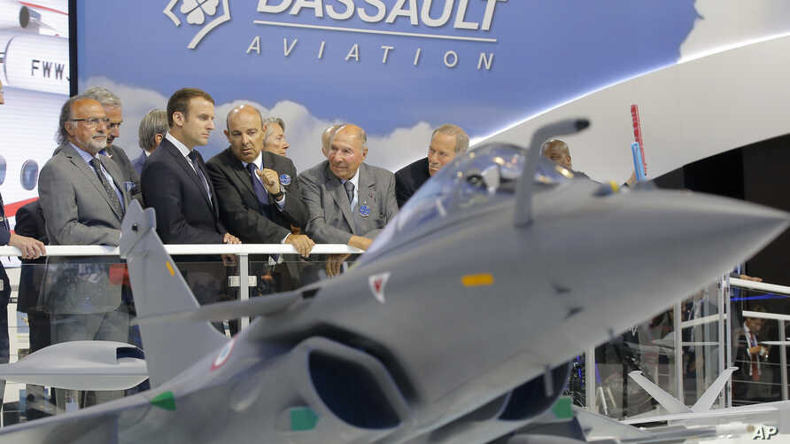French President Emmanuel Macron, second left, listens to Dassault Aviation CEO Eric Trappier, center, while visiting the Paris Air Show in Le Bourget, north of Paris, June 19, 2017.